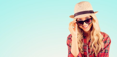 Composite image of gorgeous smiling blonde hipster posing with sunglasses