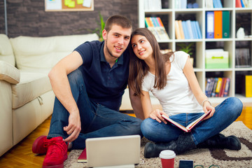 Young couple of students sitting on the floor at home and preparing for the session