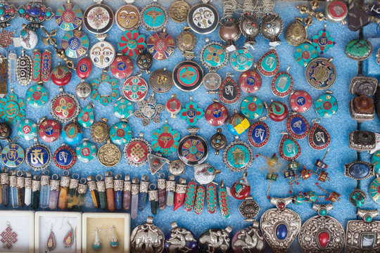 Various of different colorful Tibetan pendulums with sacred symbols in the shop at market in leh, India