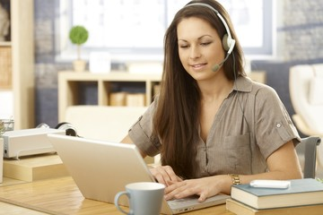 Young woman with laptop and headset