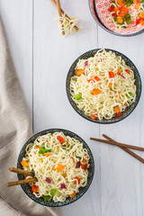 Asian noodles and vegetables on a white wood