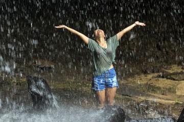 Happy woman under waterfall