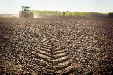 distant tractor closeup fresh track on wet spring ground