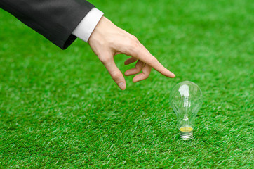 Electricity and business theme: a man in a black suit holding a light bulb against a background of green grass