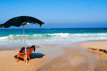 Single beach umbrella on a sandy shore