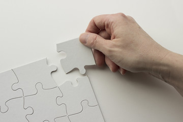 Hand places last piece of puzzle in blank white puzzle. White background.