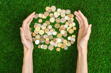 Money and Finance Topic: Money coins and human hand showing gesture on a background of green grass top view
