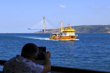 Man take picture ,boat in Bosphorus  ,bridge under construction,
