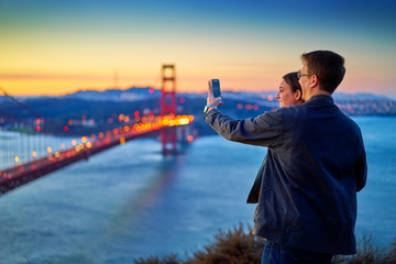 couple taking photo in front of golden gate bridge at sunrise