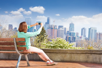 Woman take photo with cellphone of Seattle