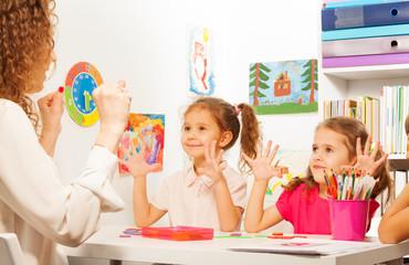 Two pupils doing finger exercises as their teacher