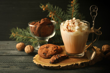 Cup of hot cacao with marshmallow and cookies on black table