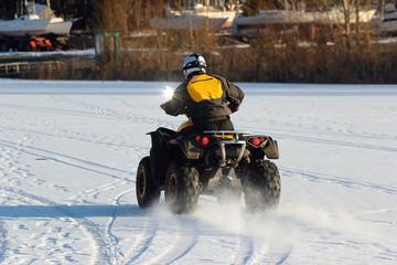 Quad bike driver rides over frozen lake