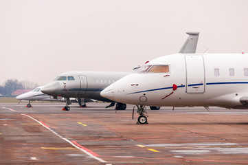 Three Commercial airplane, business jet or aircraft close up on airfield at airport