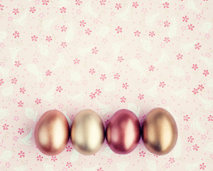 Vintage golden easter eggs over flower patterned background
