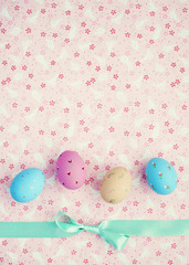 Vintage pastel easter eggs and mint ribbon over flower patterned background