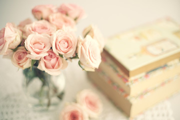 Roses in a crystal vase and books with vintage dust jackets