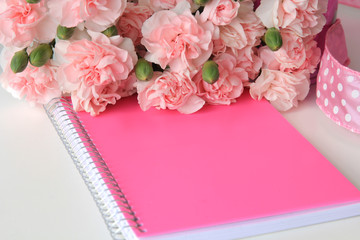 A pink notebook and bouquet of flowers with a ribbon on a white desktop background.