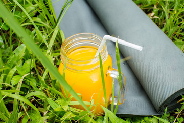 Fresh  orange juice and yoga mat on the grass