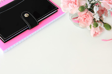 A black wallet, pink notebook and pink flowers on a white desktop background.