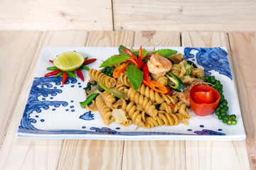 macaroni fried with spicy seafood (shrimp and squid) on wooden b