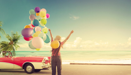 Wall Mural - Happy young woman holding colorful balloons with floating, concept of journey honeymoon in summer on tripical beach blue sky - vintage color tone