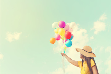 Happy young woman holding colorful balloons with floating, concept of relax in summer - vintage color tone