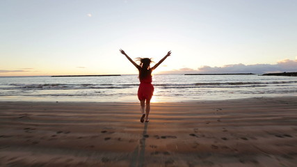 Wall Mural - Beach woman running to water in dress at sunset raising arms enjoying freedom during summer holidays vacation travel. Beautiful happy free mixed race Asian Caucasian female girl outside.