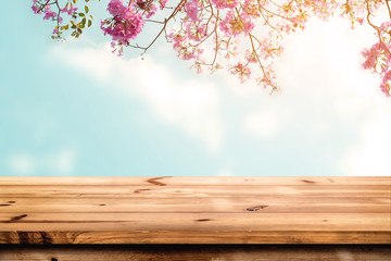 Wall Mural - Top of wood table with pink cherry blossom flower on sky background - Empty ready for your product display or montage.