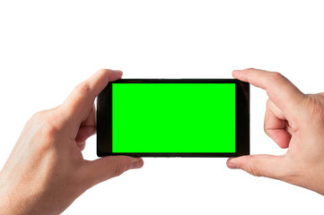 Man holds in two hands smartphone in landscape mode with green screen isolated on white. Chroma key screen for placement of your own content.