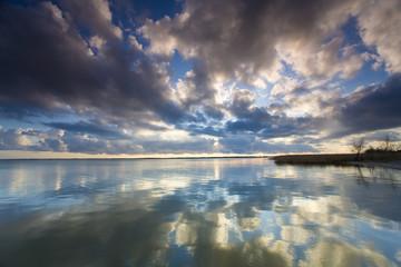 See mit ziehenden Wolken im Sonnenuntergang mit Abendrot und stimmungsvollen abendlichen Licht. Spiegelung der schönen Wolken im Wasser.