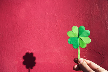 Hand holding paper origami green shamrock on pink wall background. Space for copy, lettering, text. St. Patrick's day postcard tempalte.
