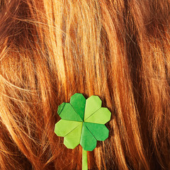 Green paper folded origami clover on red hair background. St. Patrick's day celebration. Space for copy, text, lettering.