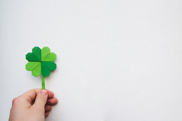 Hand holding paper origami green shamrock on white wall background. Space for copy, lettering, text. St. Patrick's day postcard tempalte.