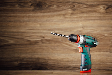 cordless drill against wooden background