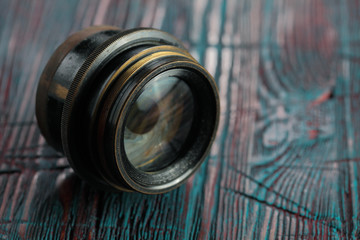Old lens from old camera on the wooden table