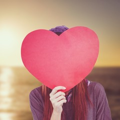 Composite image of hipster woman behind a red heart