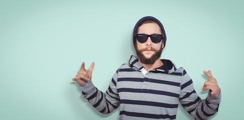 Composite image of hipster showing rock and roll hand sign
