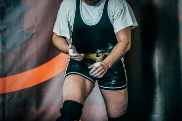 powerlifter preparing for deadlift of barbell. hands powerlifter in magnesia