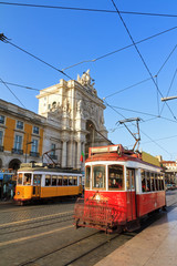 Beautiful traditional red and yellow trams in the streets of Lisbon, Portugal, in summer