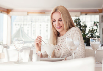 Young woman in sunny restaurant with ice-cream desert