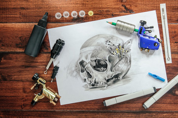 skull tattoo sketch with rotary machines, needles, grips on wooden background