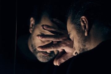 Man in despair, sad and lonely resting his head on a hand, in front of mirror