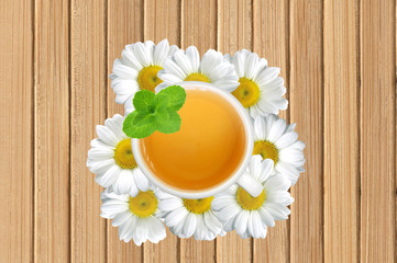 White tea cup with mint on chamomile flowers on wooden texture c