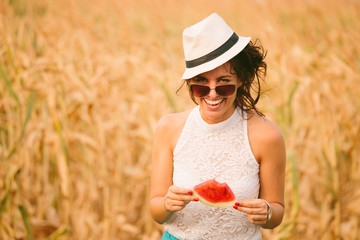 Portrait of beautiful young woman eating watermelon