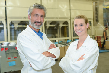 Portrait of two workers in white coats