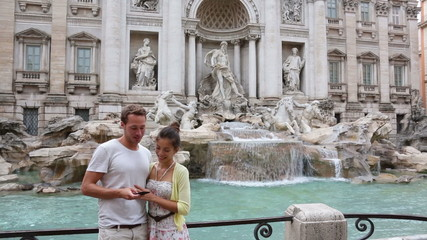 Wall Mural - Romantic couple on travel taking selfie photo by Trevi Fountain in Rome, Italy. Happy young tourists couple traveling in Europe taking self-portrait with smartphone camera. Man and woman happy.