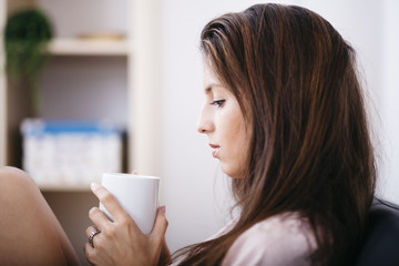 Young beautiful woman drinking a cup of tea