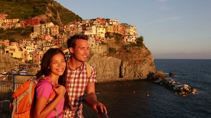 Wall Mural - Romantic couple looking at sunset on holidays travel. Young backpacking Asian woman and Caucasian man enjoying ocean view. Young people on vacation in Manarola, Cinque Terre, Liguria, Italy