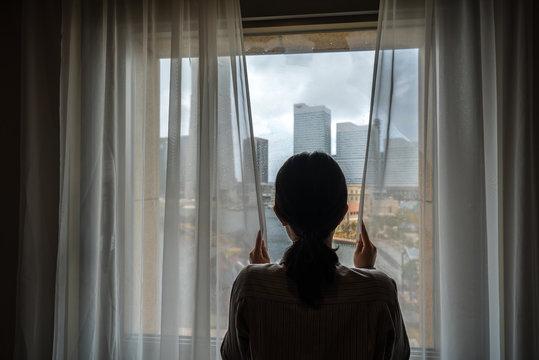 窓から都市を見る女性